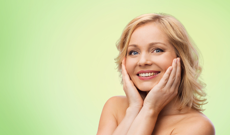 female beauty: beauty, people and skincare concept - smiling woman with bare shoulders touching face over green natural background