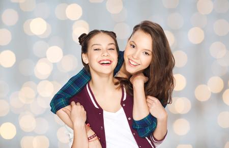 Les gens, les amis, les adolescents et le concept d'amitié - heureux souriant jolies adolescent se taisent pendant des vacances fond lumineux