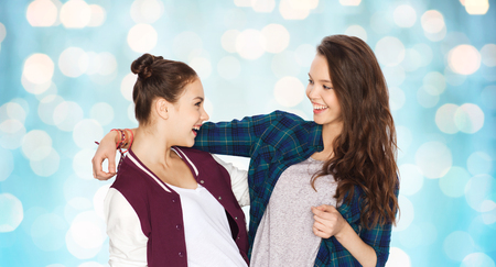 amigos abrazandose: people, friends, teens and friendship concept - happy smiling pretty teenage girls hugging over blue holidays lights background