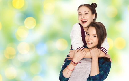 amigos abrazandose: people, friends, teens and friendship concept - happy smiling pretty teenage girls hugging over green summer holidays lights background