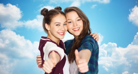 amigos abrazandose: people, friends, teens and friendship concept - happy smiling pretty teenage girls hugging and showing thumbs up over blue sky and clouds background