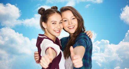 amigos abrazandose: personas, amigos, adolescentes y concepto de la amistad - sonriendo feliz Adolescentes bonitos que abrazan y que muestra los pulgares para arriba sobre el cielo azul y las nubes de fondo