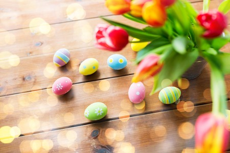 easter, holidays, tradition and object concept - close up of colored easter eggs and tulip flowers in bucket on wooden table over holidays lights
