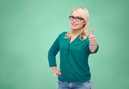 alumnos en clase: la visión, la óptica, la educación, el gesto y la gente concepto - mujer joven sonriente con gafas que muestra los pulgares para arriba sobre fondo verde de la escuela tablero de tiza