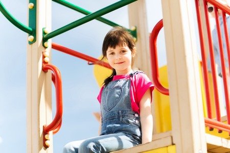 climbing frames: summer, childhood, leisure and people concept - happy little girl on playground climbing frame Stock Photo