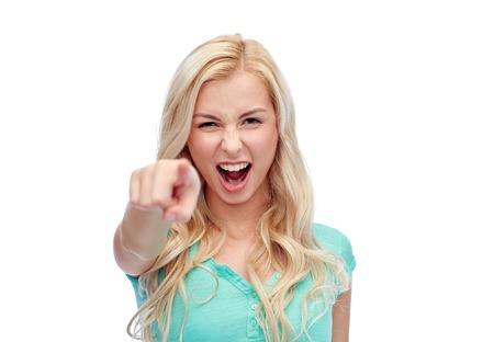 woman pointing: gesture, emotions, expressions and people concept - happy smiling young woman or teenage girl pointing finger to you Stock Photo