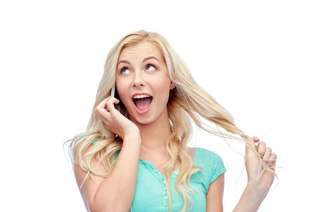 facial expression: emotions, expressions, technology and people concept - smiling young woman or teenage girl calling on smartphone Stock Photo