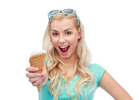 carelessness: summer, junk food and people concept - young woman or teenage girl in sunglasses eating ice cream Stock Photo