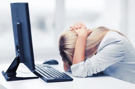 zaken, kantoor, school en onderwijs concept - benadrukt zakenvrouw met computer op het werk Stockfoto