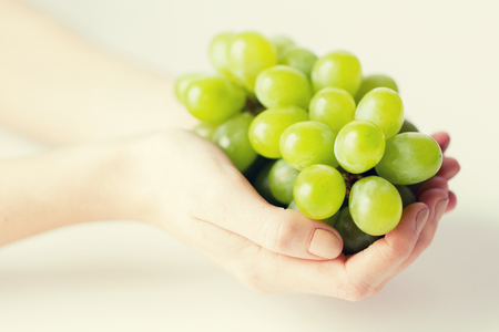 grape fruit: healthy eating, dieting, vegetarian food and people concept - close up of woman hands holding green grape bunch at home