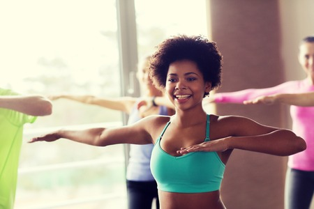 african dance: fitness, deporte, la danza y el concepto de estilo de vida - grupo de gente sonriente con el entrenador bailando en el gimnasio o estudio Foto de archivo