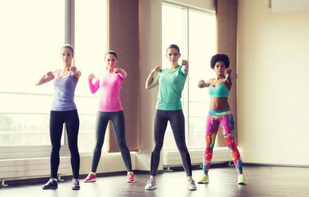 fitness, deporte, entrenamiento, gimnasio y artes marciales concepto - grupo de mujeres trabajando y luchando en el gimnasio