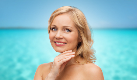 beautiful face woman: beauty, people and skincare concept - smiling middle aged woman with bare shoulders touching face over blue sea and sky background