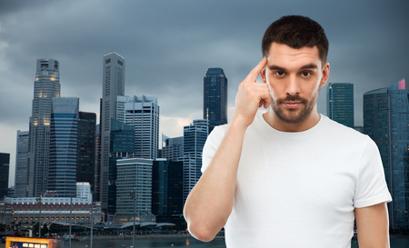 business mind: advertisement, idea, business, mind and people concept - man pointing finger to his temple over evening singapore city background Stock Photo