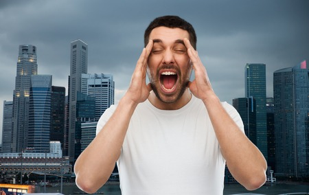 urbanization: emotions, stress, urbanization, madness and people concept - crazy shouting man in t-shirt over evening singapore city background