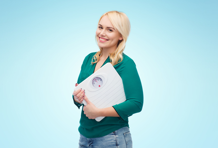 weight loss, diet, slimming, plus size and people concept - smiling young woman holding scales over blue background