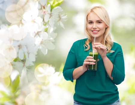 green vegetable: healthy eating, vegetarian food, diet, detox and people concept - smiling young woman drinking green vegetable juice or smoothie from glass over natural cherry blossom background