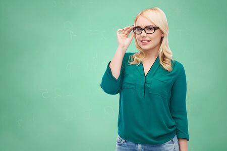 overweight students: vision, optics, education and people concept - smiling young woman with eyeglasses over green school chalk board background