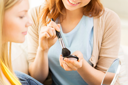 visagiste: beauty, make up, cosmetics and people concept - close up of smiling young woman and visagist or friend with blush and makeup brush