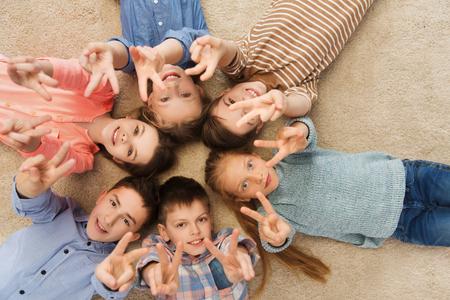 caras felices: la infancia, la moda, la amistad y el concepto de personas - niños sonriendo feliz que muestra la mano de la paz y acostado en círculo floorin Foto de archivo