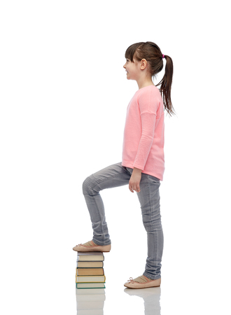 childhood, school, education and people concept - happy little girl stepping on book pile Stock Photo