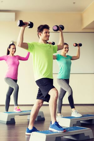 Weights: fitness, sport, aerobics and people concept - group of smiling people working out with dumbbells flexing muscles on step platforms in gym