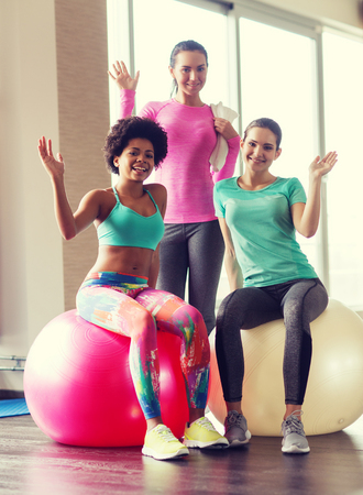 fitball: fitness, sport, training and lifestyle concept - group of smiling women with exercise balls in gym