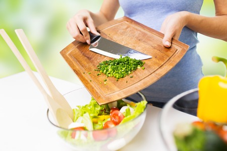adding: healthy eating, cooking, vegetarian food, diet and people concept - close up of woman adding chopped green onion to salad Stock Photo