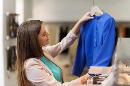 venta, compras, moda, estilo y concepto de la gente - mujer joven feliz elegir la ropa en centro comercial o tienda de ropa