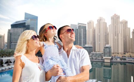 summer holidays, tourism, vacation, travel and people concept - happy family over dubai city waterfront background