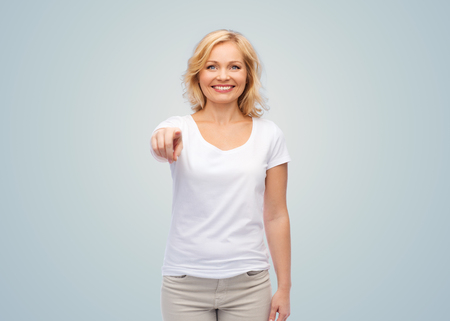 casual woman: gesture, advertisement and people concept - smiling woman in blank white t-shirt pointing finger to you over gray background