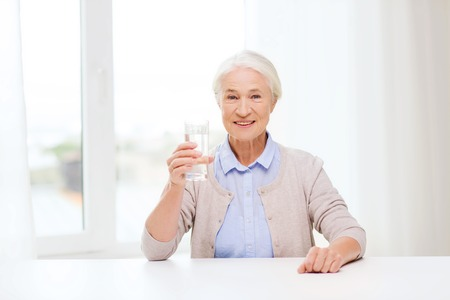 acqua bicchiere: l'età, l'assistenza sanitaria e la gente concetto - donna felice senior con un bicchiere di acqua in casa