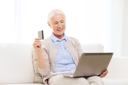 emoney: technology, age and people concept - happy senior woman with laptop compute and credit or bank card r at home