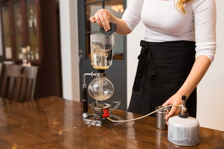 siphon: equipment, coffee shop, people and technology concept - close up of woman with butane gas burner heating water in siphon coffeemaker at cafe bar or restaurant kitchen Stock Photo