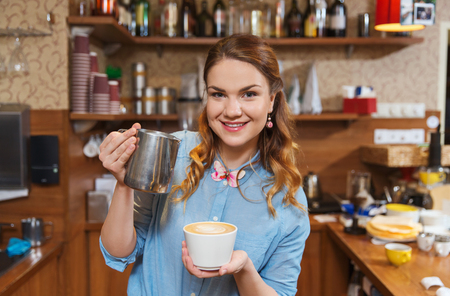 equipment, coffee shop, people and technology concept - barista woman pouring cream to cup of coffee at cafe bar or restaurant kitchen Stock Photo