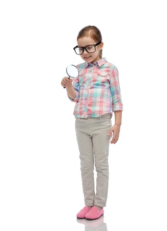 elementary schools: childhood, education, investigation, discovery and people concept - happy little girl in eyeglasses with magnifying glass