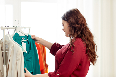 La ropa, la moda, el estilo y el concepto de la gente - la ropa Feliz más mujer de la talla de elegir en el armario en casa Foto de archivo - 68090156
