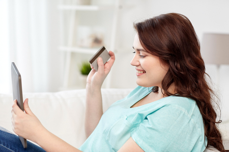 emoney: people, internet bank, online shopping, technology and e-money concept - happy young plus size woman sitting on sofa with tablet pc computer and credit card at home