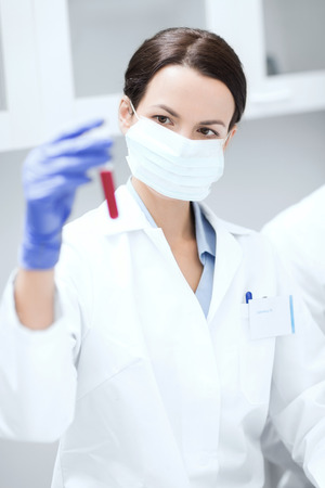 science, chemistry, biology, medicine and people concept - close up of young female scientist holding test tube with blood sample making research in clinical laboratory Stock fotó