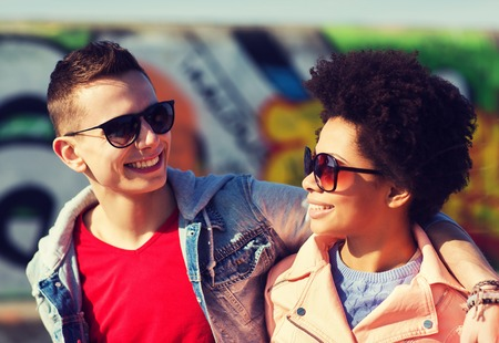 trave: friendship, tourism, trave, relations and people concept - group of happy teenage friends in sunglasses hugging outdoors Stock Photo