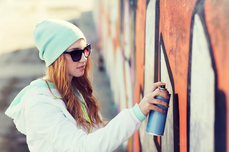 people, art, creativity and youth culture concept - young woman or teenage girl drawing graffiti with spray paint on street wall Banque d'images