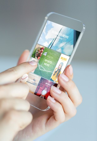 body parts cell phone: business, technology, internet and people concept - close up of woman hand holding and showing transparent smartphone with news web pages on screen Stock Photo