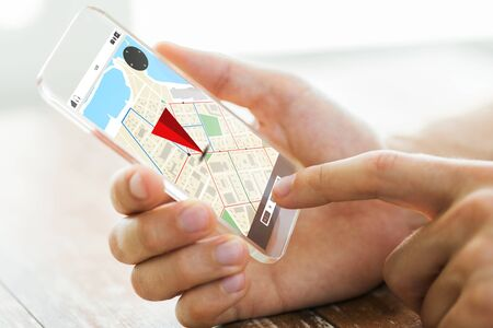 navigation, location, technology and people concept - close up of male hand holding transparent smartphone with gps navigator map on screen