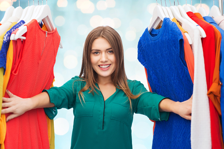woman closet: clothing, fashion, style and people concept - happy woman choosing clothes at wardrobe over blue holidays lights background
