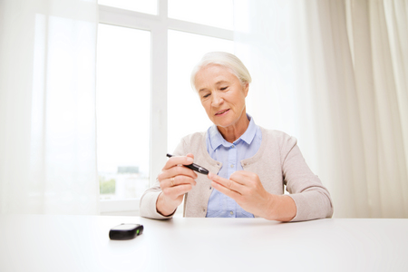 home health care: medicine, age, diabetes, health care and people concept - happy senior woman with glucometer checking blood sugar level at home