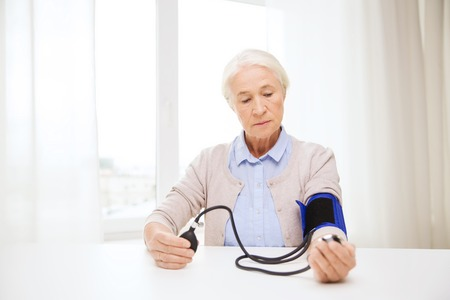 home health care: medicine, age, health care and people concept - senior woman with tonometer checking blood pressure level at home