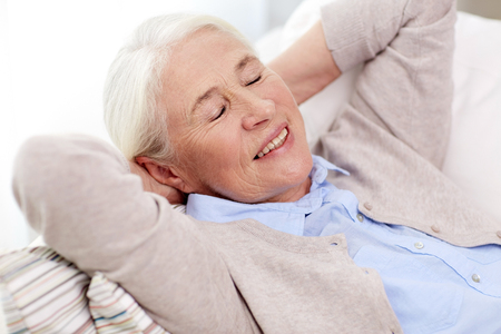 closed up: age, relax and people concept - happy smiling senior woman resting on sofa and dreaming at home
