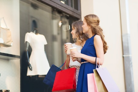 sale shop: sale, consumerism and people concept - happy young women with shopping bags and coffee paper cups looking at shop window outdoors Stock Photo