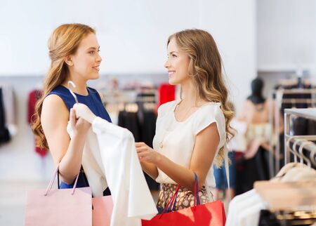 clothing shop: sale, consumerism and people concept - happy young women with shopping bags choosing clothes at clothing shop Stock Photo