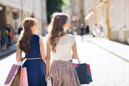 city centre: sale, consumerism and people concept - happy young women with shopping bags walking along city street